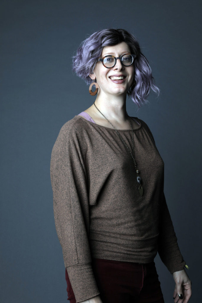 A portrait of Sasha with purple shoulder length hair, brown round glasses, a brown sweater.